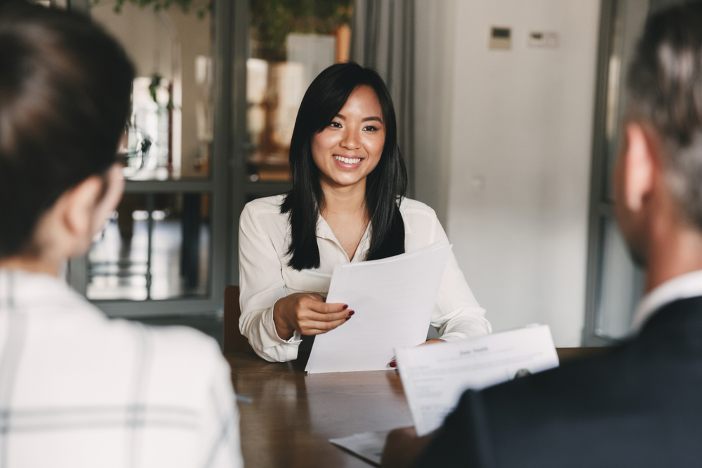 Job hunter at interview holding a resume in front of recruiters