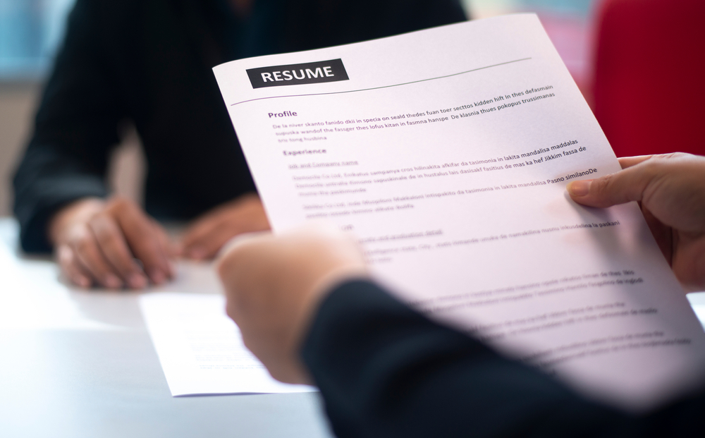 Interviewer holding a resume.